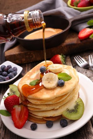 Photo for Sweet pancakes with fruits on plate on table - Royalty Free Image