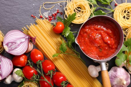 Photo for Raw spaghetti, tomato sauce and ingredients on table - Royalty Free Image