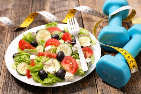 Photo for Diet food concept with salad, measuring tape, dumbbels - Royalty Free Image