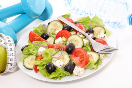 Photo for Healthy eating concept. salad, dumbbells and water - Royalty Free Image