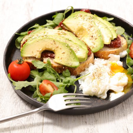 Photo for Avocado toasts and poached egg in frying pan - Royalty Free Image