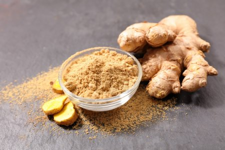 Photo for Ginger root spice powder in bowl - Royalty Free Image