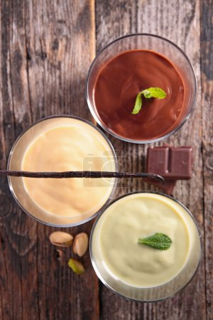 Photo for Mousse assortment with mint on wooden table, top view - Royalty Free Image