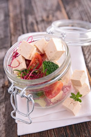 Photo for Fresh salad with tofu, tomatoes and broccoli in jar, close up - Royalty Free Image