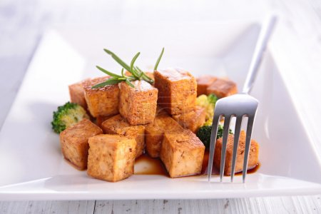 Photo for Grilled tofu with broccoli and herb on plate served on wooden table, close up - Royalty Free Image
