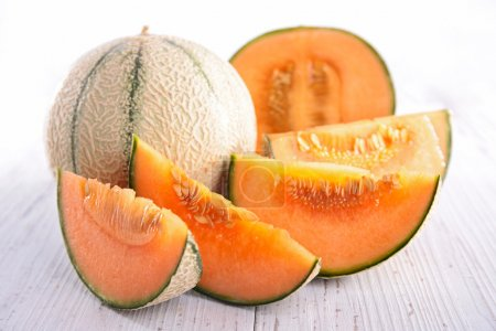 Photo for Whole and sliced bright melon served on light wooden table - Royalty Free Image