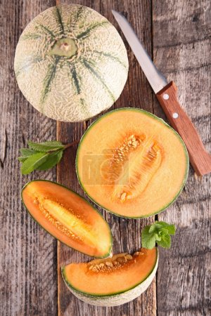 Photo for Whole and sliced bright melon with mint served on wooden table, top view - Royalty Free Image