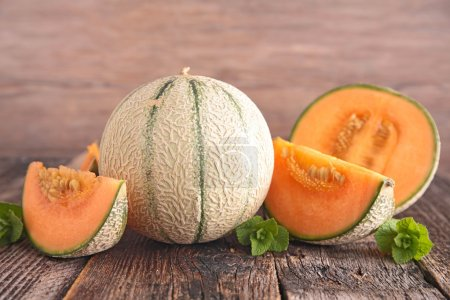 Photo for Whole and sliced bright melon with mint served on wooden table - Royalty Free Image