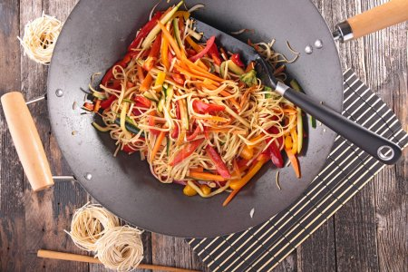 Photo for Asian cuisine with tasty sliced vegetables in black pan, close up - Royalty Free Image