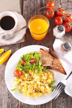 Photo for Tasty and healthy breakfast  of scrambled egg, salad and toasts with fresh juice on wooden table, top view - Royalty Free Image