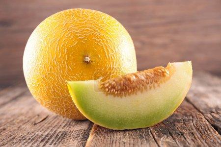 Photo pour Melon de miel sucré entier et tranché sur fond en bois - image libre de droit