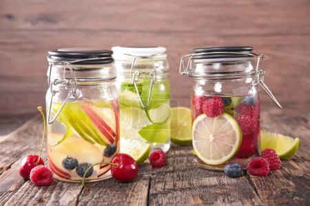 Photo for Detox water with different tastes in glass jars with sticks on wooden table ,close up - Royalty Free Image