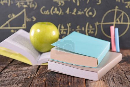 Photo for School study concept with books and apple on blackboard with math formulas - Royalty Free Image