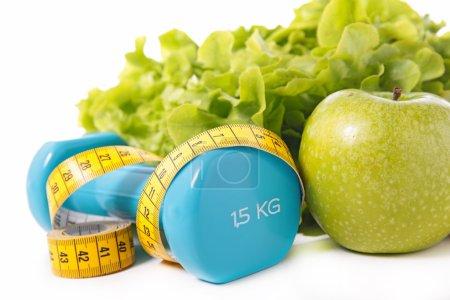 Photo pour Alimentation saine et concept de régime. laitue verte, pomme, haltère et ruban à mesurer - image libre de droit