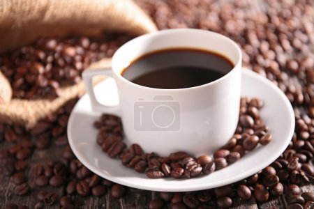 Photo for Coffee cup with beans on saucer on table - Royalty Free Image