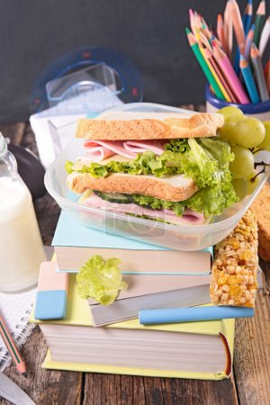 Photo for Sandwich and book, school concept. close up on wooden table - Royalty Free Image