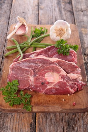 Photo for Raw meat steak with herbs on wooden board - Royalty Free Image