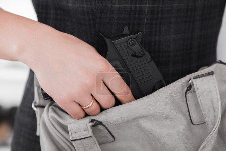 Photo pour Femme avec une arme dissimulée - image libre de droit