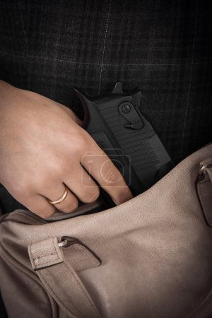 Modern personal weapon in woman brown leather handbag