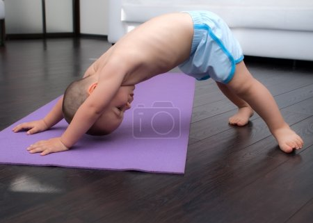 Photo for Little boy trains on a yoga Mat, age 2 years - Royalty Free Image