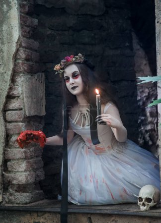 Photo pour Creepy dead bride with bloody meat and candle in hand. Halloween scene - image libre de droit
