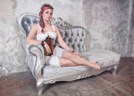 Beautiful steampunk woman on the sofa