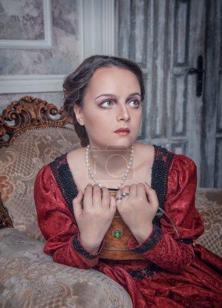 Photo pour Belle jeune femme en robe médiévale rouge sur le fauteuil - image libre de droit