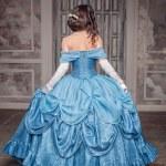 Beautiful medieval woman in long blue dress, back...