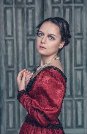 Photo pour Portrait de jeune belle femme médiévale en robe rouge - image libre de droit