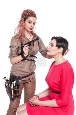Photo pour Maquilleuse professionnelle en maquillage à un modèle isolé sur fond blanc - image libre de droit