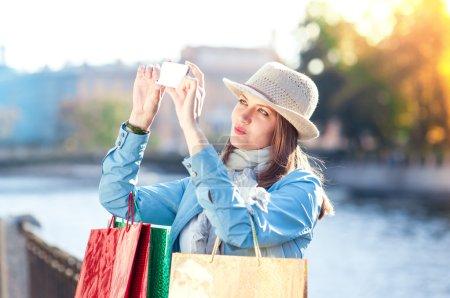 Photo pour Belle fille avec des sacs à provisions pris en photo d'elle-même dans la ville en plein air - image libre de droit