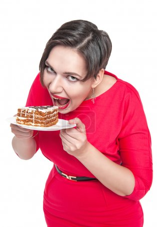 Photo for Beautiful plus size woman eating cake isolated over white - Royalty Free Image