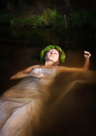 Young beautiful drowned woman with fern wreath lyi...
