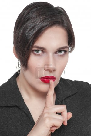 Beautiful plus size woman with finger on lips isolated