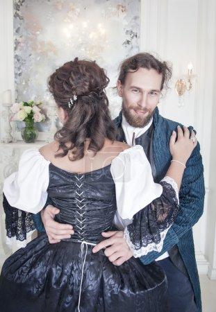 Handsome man untying corset of woman in medieval dress