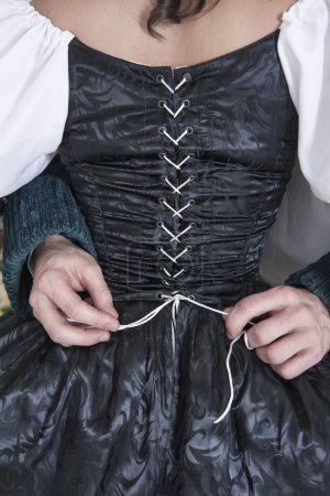 Man hands untying corset of woman in medieval dress