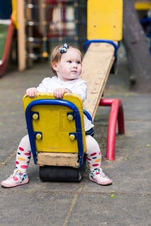 Cute baby girl on a seesaw swing