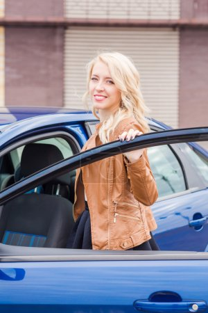 Beautiful happy young girl standing near her car