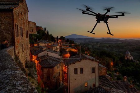 Photo for A silhouette of a flying drone with a dramatic sunset in the background in the skies of old European city - Royalty Free Image