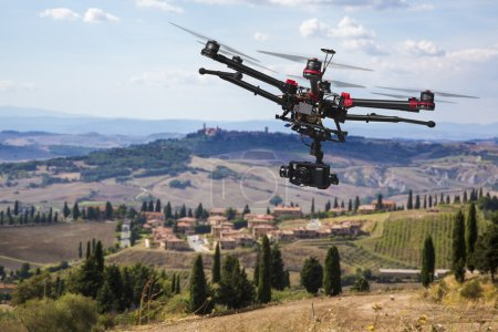 Photo for A flying helicopter with raised landing gears and a camera with blured hills of Tuscany in the background - Royalty Free Image