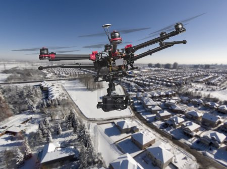Photo for A drone with a camera and raised landing gears flying high above a residential area covered with fresh snow in a bright sunny winter day. - Royalty Free Image