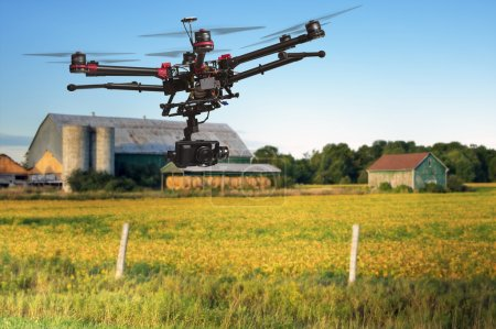 Photo for A flying helicopter with raised landing gears and a camera with blurred crop field and farm structures on a background highlighted by a sunset - Royalty Free Image