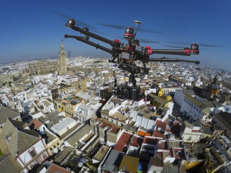 Photo for An aerial view of a flying multi-copter with raised landing gears and a camera with slightly blured center of old Seville in the background - Royalty Free Image