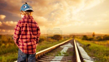 Foto de Niño pequeño de pie en el campo raillway puesta de sol de verano - Imagen libre de derechos