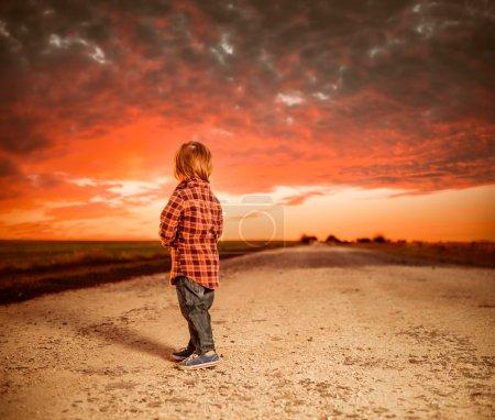 Foto de Niño en el camino del campo mirando a través del horizonte - Imagen libre de derechos