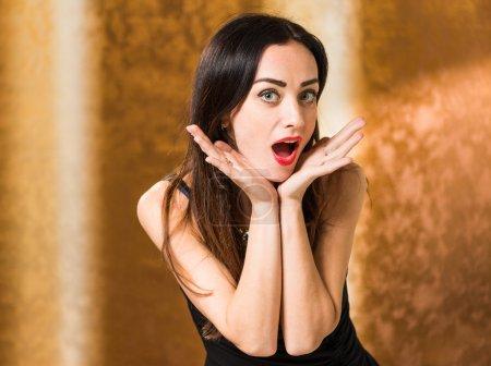 Photo pour Jeune femme brune avec une expression surprise à fond doré - image libre de droit