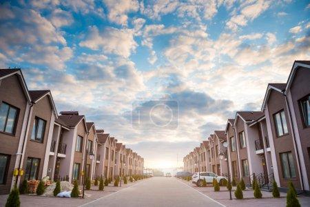 Photo pour Nouvelles maisons de construction au coucher du soleil de la rue - image libre de droit