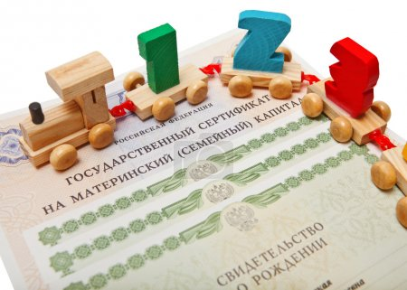 Russian certificate for maternity capital with birth certificates and children's train with figures