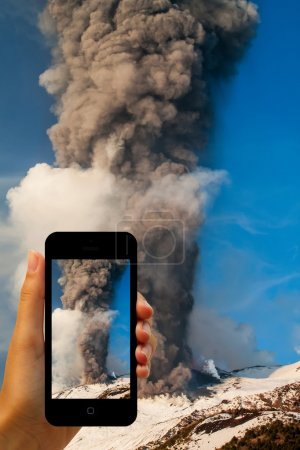 Tourist photographing the volcano eruption on smartphones