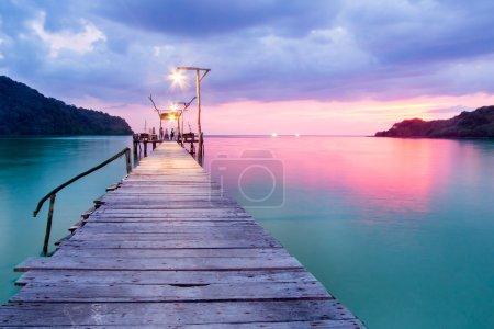 Wooden bridge in the port over sea between sunset...